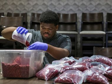 Demondric Pratt helps prepare food packets for meal kits to be distributed by Cafe Momentum to needy students and their families.