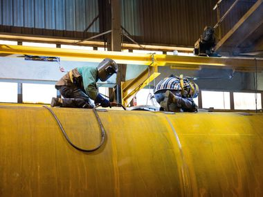 Welders for Dallas-based Trinity Industries work on a crude oil tank car at the company's plant in Saginaw.