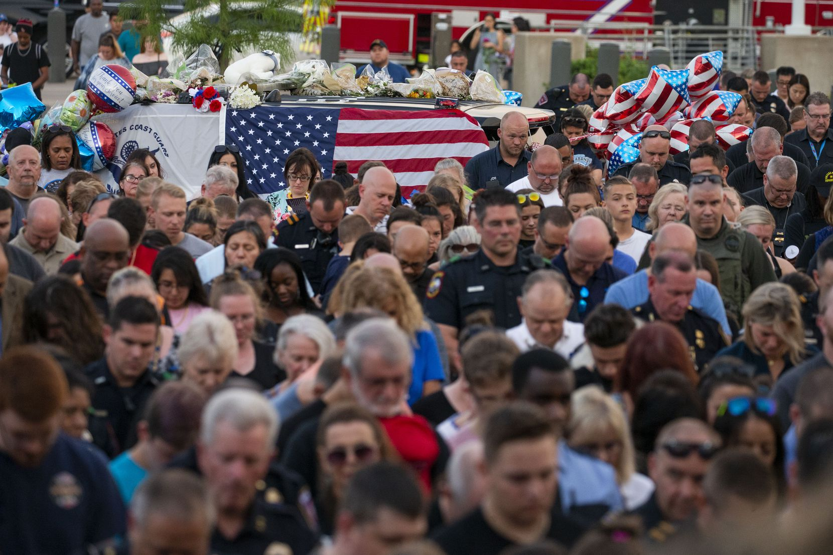 "Attendees bow their heads during a vigil Sunday for Grand Prairie police Officer Albert ""A.J."" Castaneda at the Grand Prairie Public Safety Building."