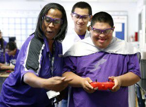 Senior Javier Guerrero (right) drives a robot alongside his special education teacher Pauline Tatum and Cesar Sauceda during an after-school robotics team meeting for special education students at Sunset High School. (Rose Baca/Staff Photographer)