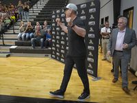 Troy Aikman walks into the gymnasium to surprise students during a pep rally at Henryetta High School on Friday.  (Smiley N. Pool/The Dallas Morning News)