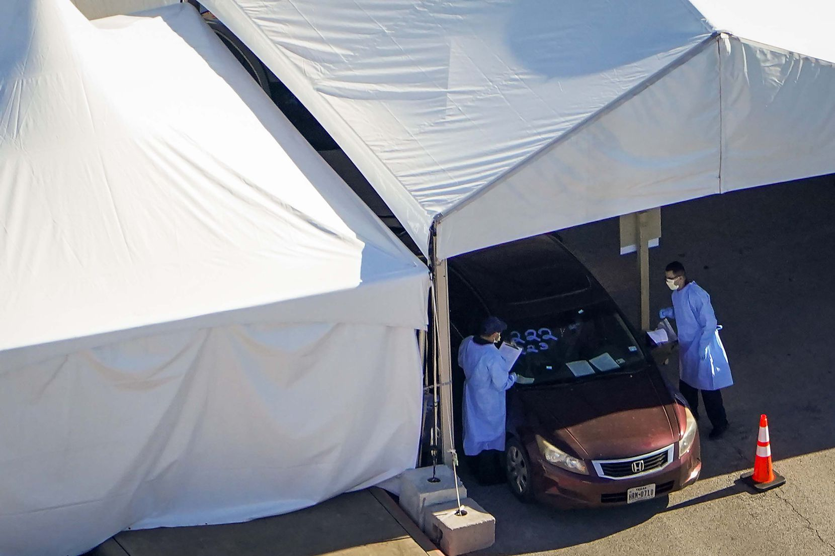 Aerial view of medical professionals working at a Dallas County drive-through COVID-19 testing site at Ellis Davis Field House in southern Dallas on March 24, 2020.
