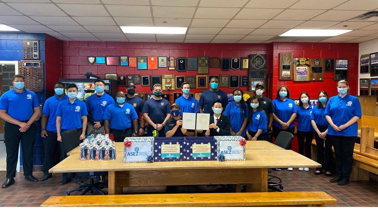 The Elohim Bible Study Club at UT-Arlington poses with Dallas Fire-Rescue members after donating masks to the department on July 26.