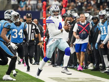 Dallas Cowboys quarterback Dak Prescott (4) scrambles for a first down against Carolina Panthers cornerback Juston Burris (31) during the first half an NFL football game at AT&T Stadium on Sunday, Oct. 3, 2021, in Arlington.