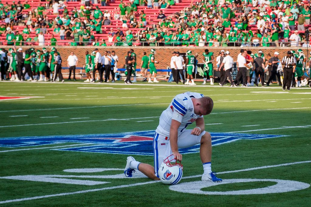 SMU quarterback Shane Buechele kneels in prayer at the 20-yard line before an NCAA football game against UNT at Ford Stadium on Saturday, Sept. 7, 2019, in Dallas. (Smiley N. Pool/The Dallas Morning News)