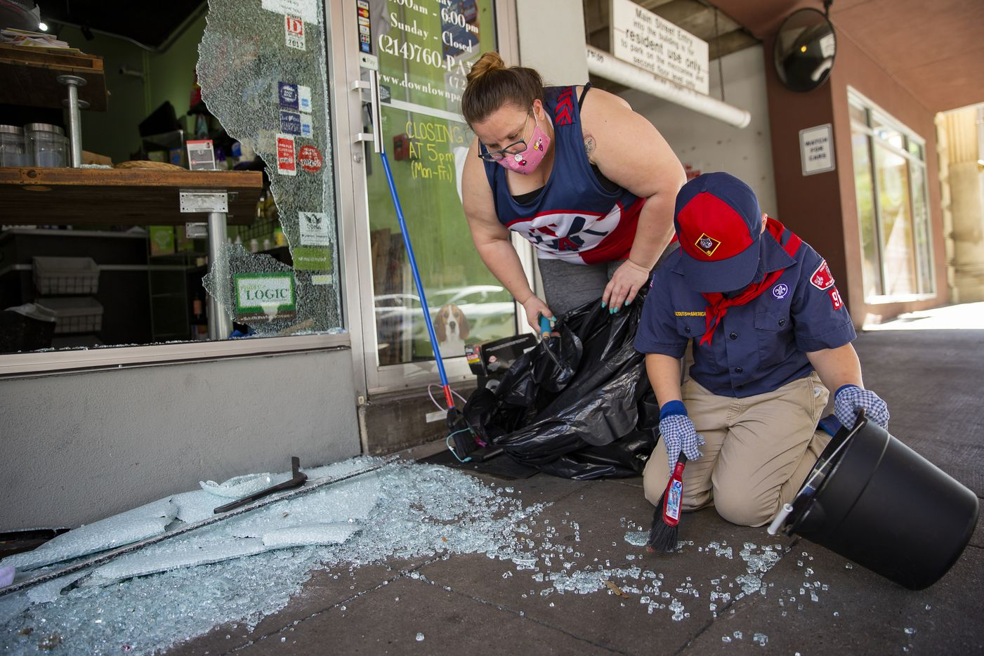 Julie Farmer from Seagoville, TX, and her son Kinsler Farmer, 7, volunteer to clean up after it was hit during last night's protest on Saturday morning, May 30, 2020 in Downtown Dallas. Farmer said she wants to teach youth what it means to come and be a community.