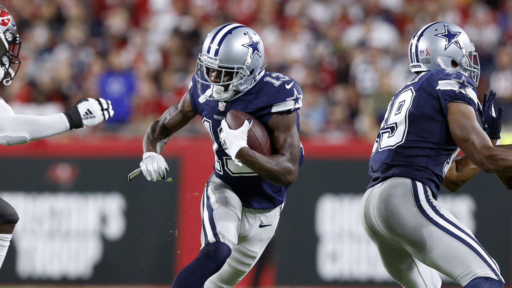Dallas Cowboys wide receiver Michael Gallup (13) receives a block from fellow wide receiver Amari Cooper (19) during the first half at Raymond James Stadium in Tampa, Florida, Thursday, September 9, 2021. The Cowboys faced the Tampa Bay Buccaneers in the NFL season opener.
