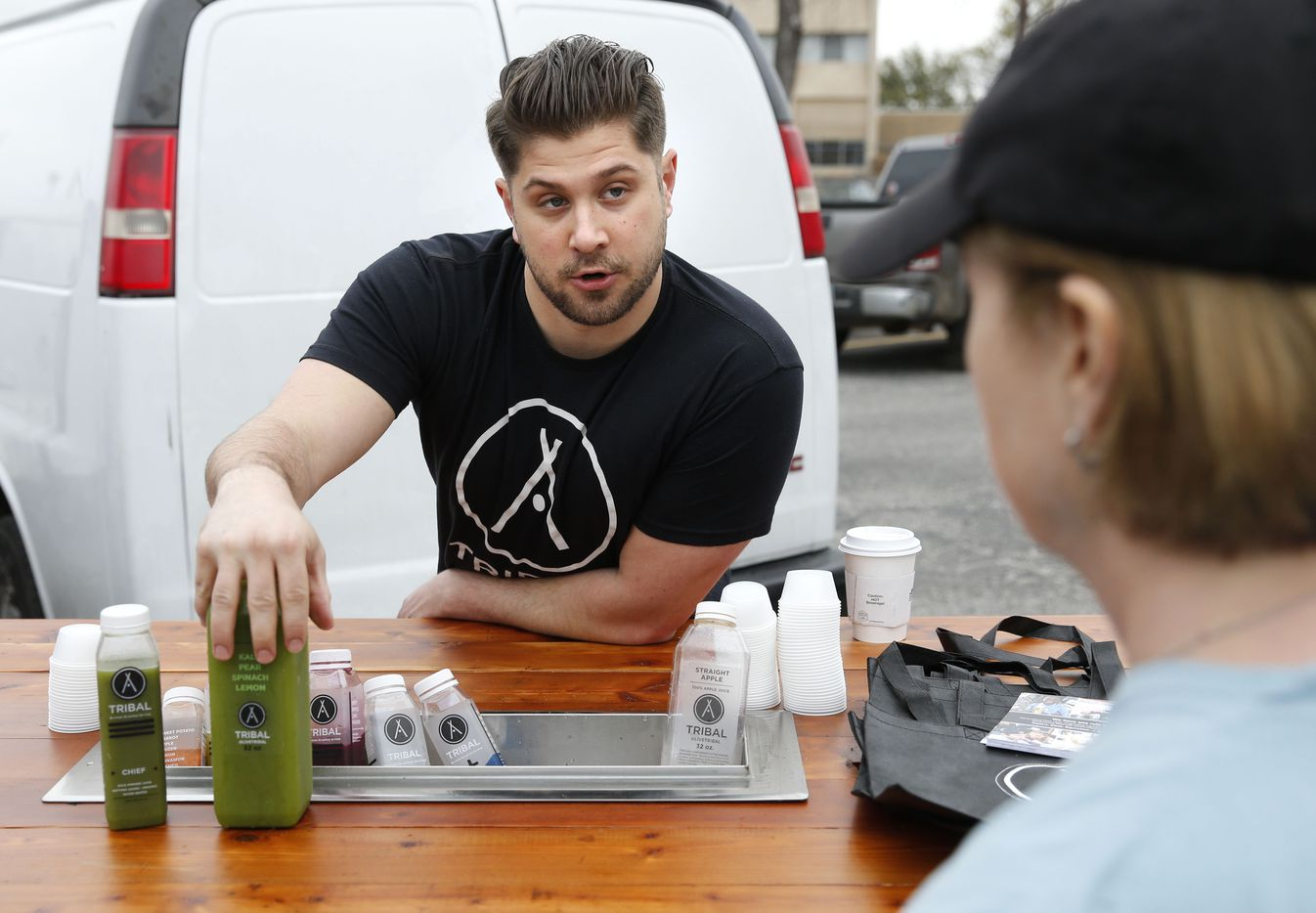 Tribal's Brenton Phillips of Dallas explains the different types of juices they carry to Terry Moomaw of Dallas during opening day for the Tyler Street Market run by Good Local in Dallas on Saturday, March 18, 2017.
