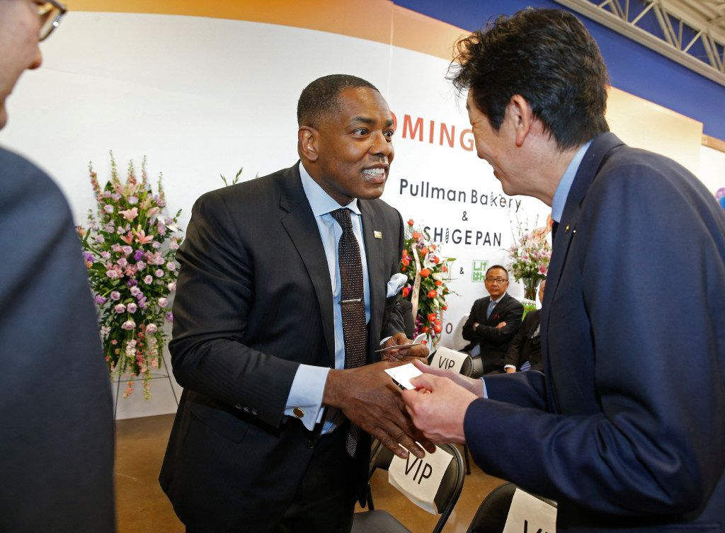 Plano Mayor Harry LaRosiliere (left) shakes the hand of Tetsuo Ogawa, executive vice president of Toyota, during the grand opening of the Mitsuwa Market place in Plano, Texas on April 14, 2017. (Nathan Hunsinger/The Dallas Morning News)