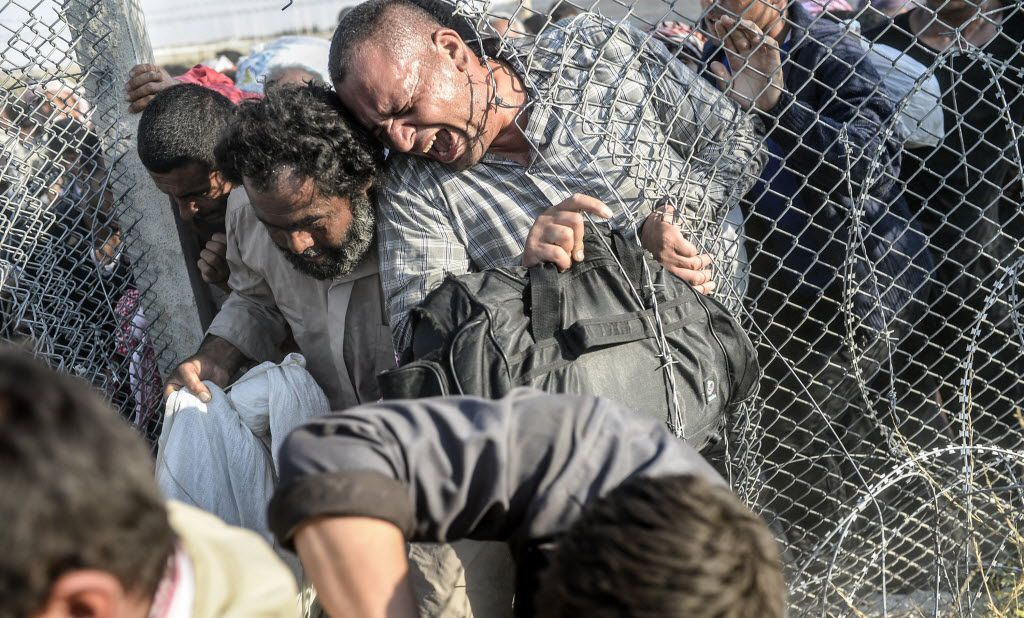 """Syrians fleeing the war pass through border fences to enter Turkish territory illegally, near the Turkish border crossing at Akcakale in Sanliurfa province on June 14, 2015. Agence France-Presse photographer Bulent Kilic was honored on Sept. 5, 2015 at photojournalism's biggest annual festival for dramatic images of refugees fleeing across the Turkish border. Kilic, 35, won the Visa d'Or for News, the most prestigious award handed out at the """"Visa Pour L'Image"""" festival in Perpignan, southwestern France."""