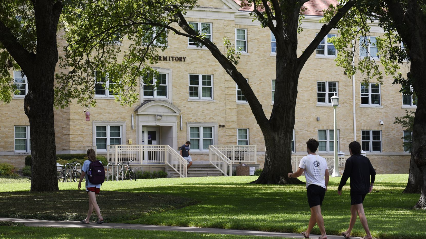 Texas Christian University students walk toward the Clark Hall dormitory on the campus of TCU in Fort Worth on Aug. 27, 2020.