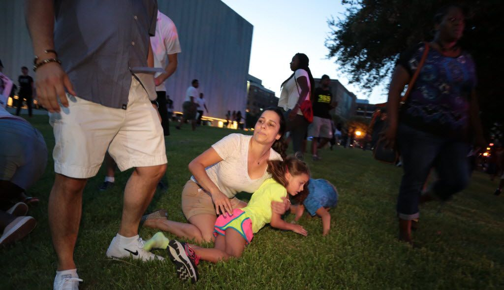 A mother covers her children as Dallas police respond to shots being fired during a protest over recent fatal shootings by police in Louisiana and Minnesota, Thursday, July 7, 2016, in Dallas. Maria R. Olivas/Special Contributor