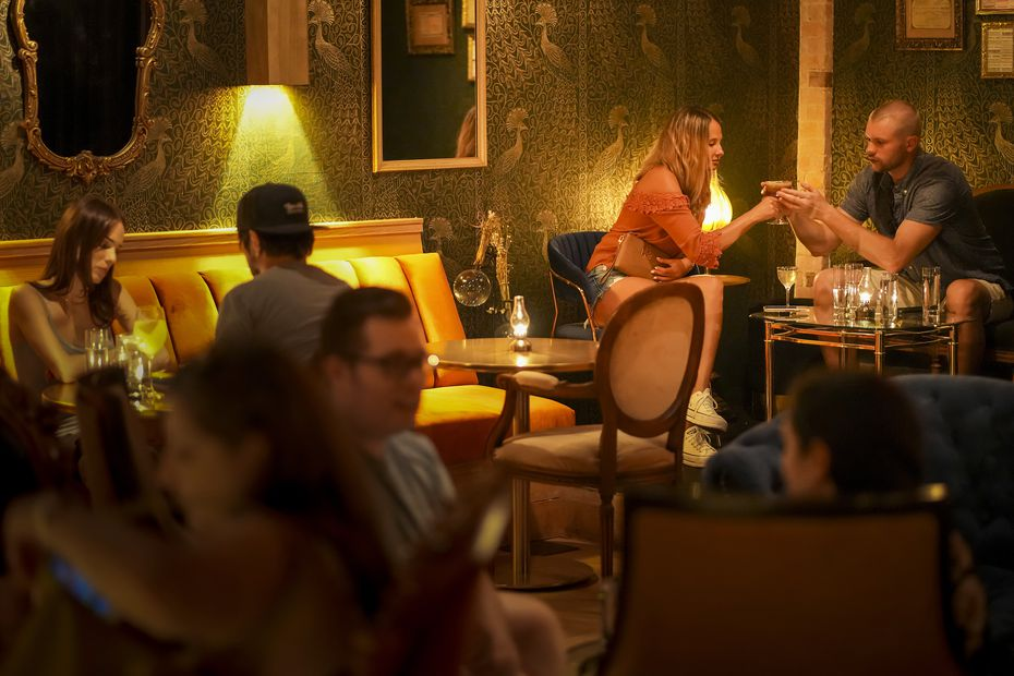 Heather Lustig and Jack Beale (in corner at top right) share a drink at Apothecary, a new speakeasy on Lowest Greenville in Dallas.