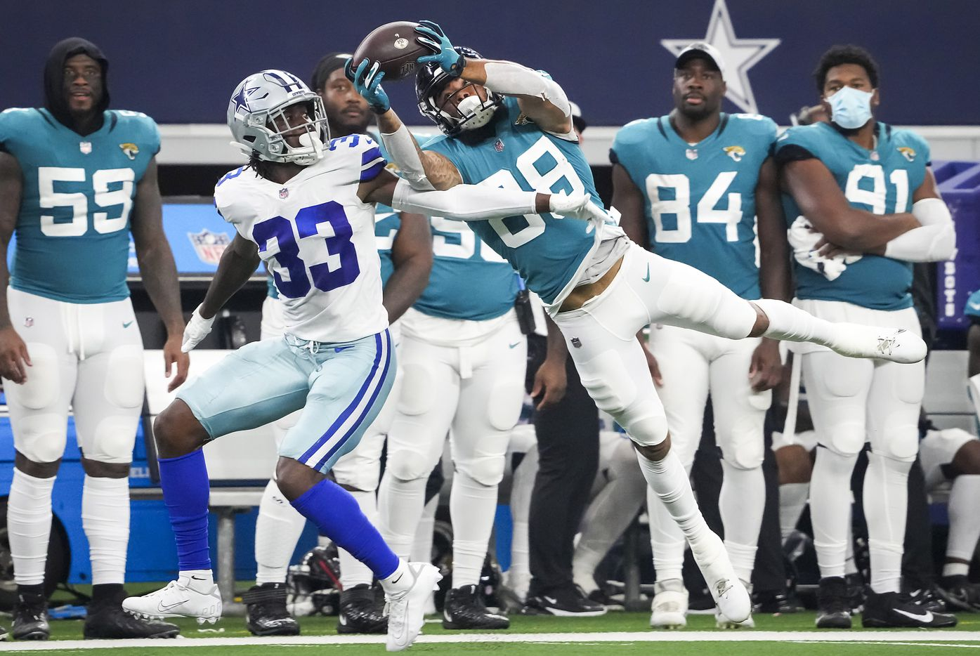 Jacksonville Jaguars wide receiver Jeff Cotton, Jr., (88) hauls in a long pass as Dallas Cowboys defensive back Deante Burton (33) defends during the first half of a preseason NFL football game at AT&T Stadium on Sunday, Aug. 29, 2021, in Arlington. (Smiley N. Pool/The Dallas Morning News)