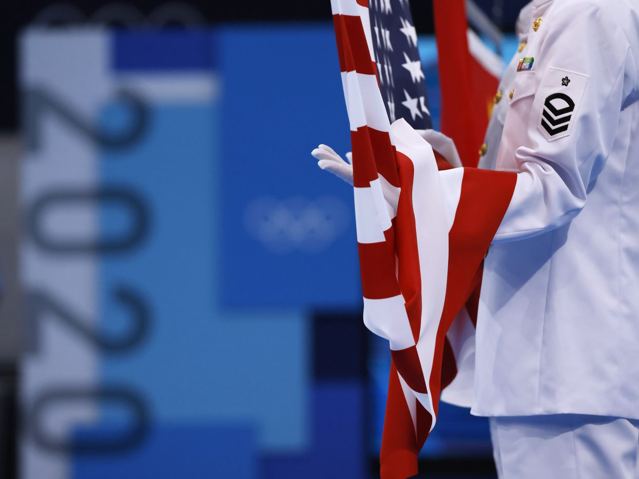 Flags are hoisted in the air during the medal ceremony for the women's 3 meter springboard final during the postponed 2020 Tokyo Olympics at Tokyo Aquatics Centre, on Sunday, August 1, 2021, in Tokyo, Japan. USA's Krysta Palmer finished 3rd with a total score of 343.75 to earn a bronze medal. (Vernon Bryant/The Dallas Morning News)