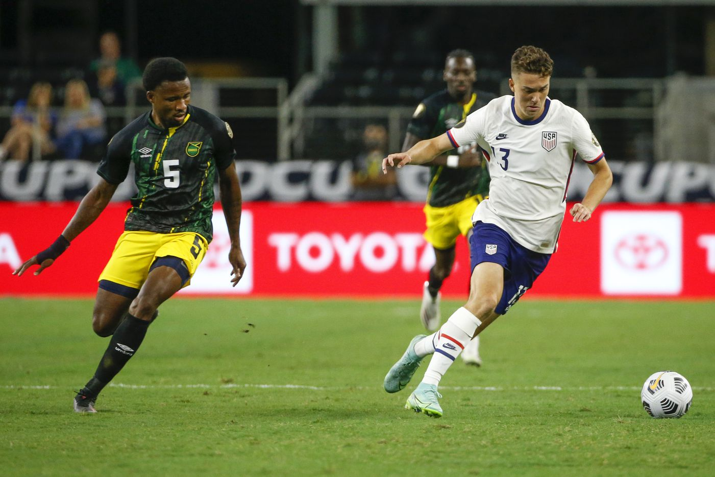 USA forward Matthew Hoppe (13) dribbles away from Jamaica defender Alvas Powell (5) during the first half of a CONCACAF Gold Cup quarterfinal soccer match at AT&T Stadium on Sunday, July 25, 2021, in Arlington. (Elias Valverde II/The Dallas Morning News)
