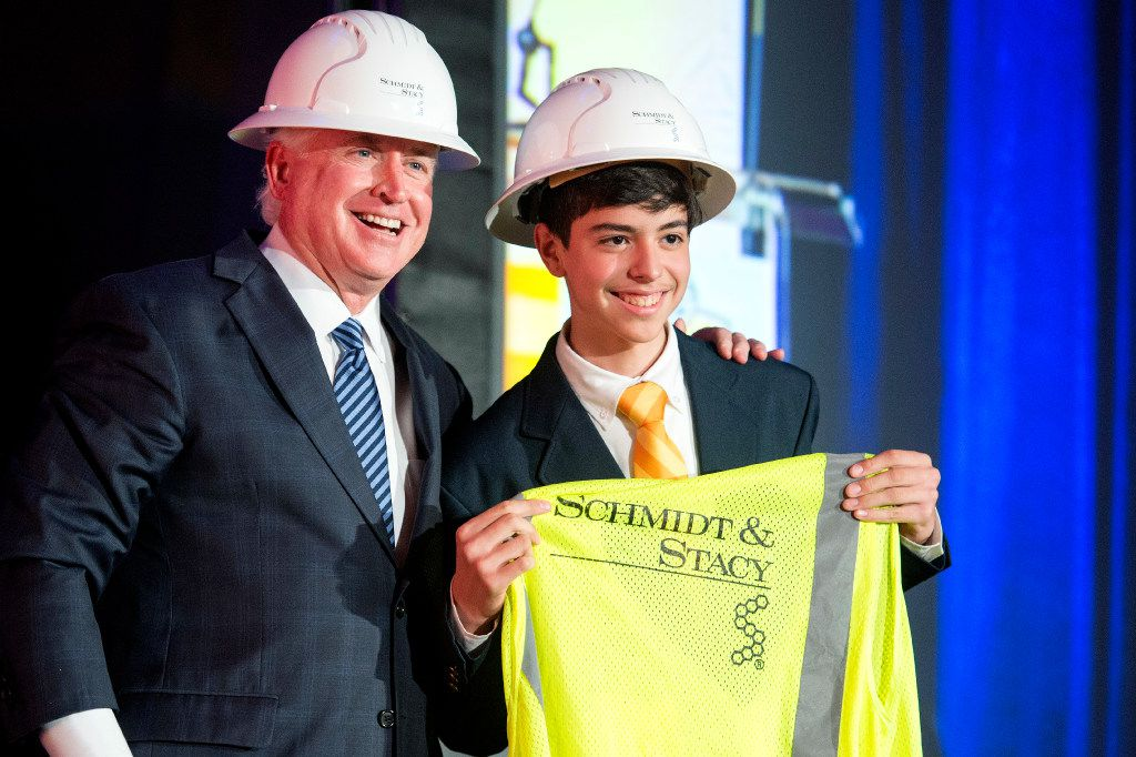 Pablo Corona, a 14-year-old incoming freshman at Cristo Rey Dallas College Prep, is drafted to his work assignment by David Schmidt, president of the engineering firm Schmidt & Stacy, during Cristo Rey's Draft Day ceremony on July 28, 2017, at Cristo Rey Dallas College Prep in Dallas. Through the school's Corporate Work Study Program, students work one day a week with local businesses to earn a portion of their tuition.