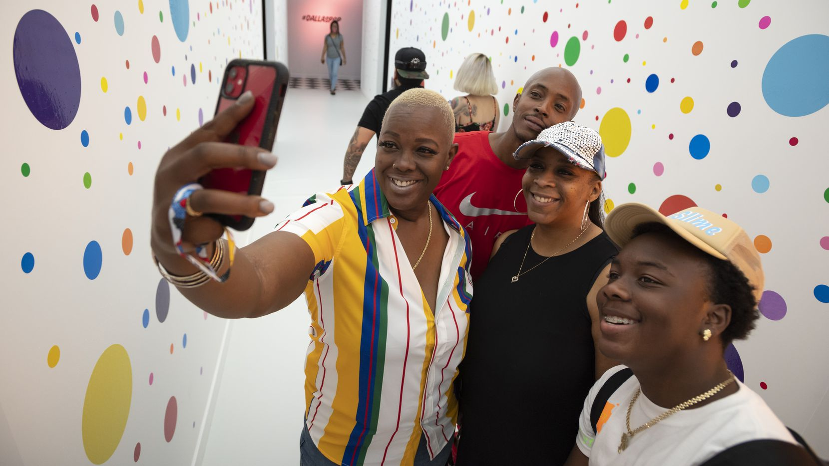 Yolanda Miller snaps a selfie with Tyvone Barnes (in red), Tanika Myricks (second from right) and Rain Johnson (right) in a hallway of the multiroom Pop! by Snowday.