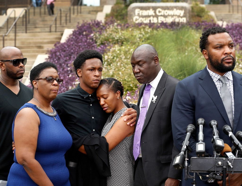 Brandt Jean, brother of shooting victim Botham Jean (third from left), hugs his sister Allisa Charles-Findley, during a press conference outside the Frank Crowley Courts Building. He was joined by his mother, Allison Jean (left) and attorney Benjamin Crump (second from right). Their attorney Lee Merritt (right) speaks to the media.