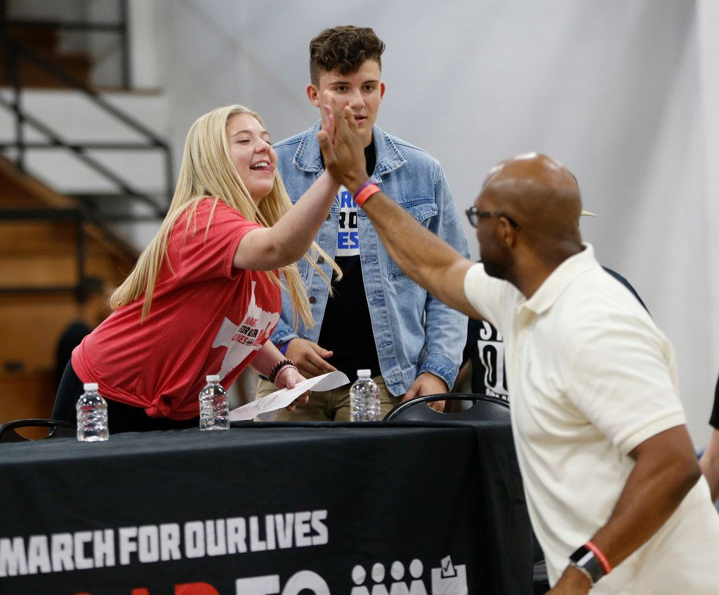Jaclyn Corin (left) high-fives Michael Sorrell, president of Paul Quinn College, during a panel with students from Stoneman Douglas High School from Parkland, Fla., that was held at Paul Quinn College in Dallas on July 7, 2018.