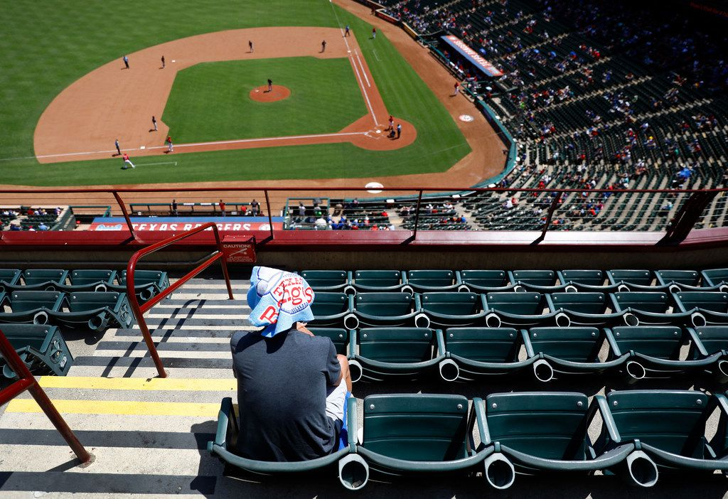 Optimists and pessimists can agree: based on official attendance numbers, Globe Life Park was less than half full, leaving Texas Rangers fan Don Scheibel of McKinney with several sections to himself in the upper concourse as temperatures climbed to 108¼ at Globe Life Park in Arlington, Sunday, July 22, 2018.  It was one of the hottest games on record.  The Rangers won, 5-0. (Tom Fox/The Dallas Morning News)