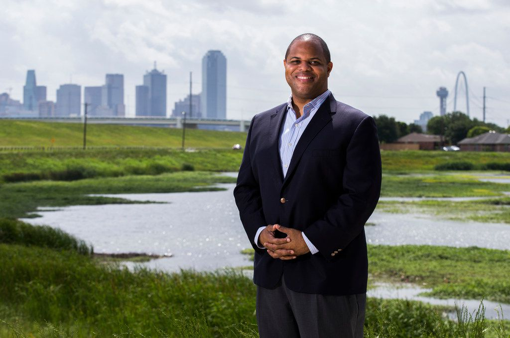 State Rep. and Dallas mayoral candidate Eric Johnson poses for a photo in the former Los Altos neighborhood where he grew up in West Dallas. Johnson said he played in the grass behind him, and he and his friends would swing on a swing set that overlooked the Dallas skyline. He lived in an apartment complex that was torn down many years ago.