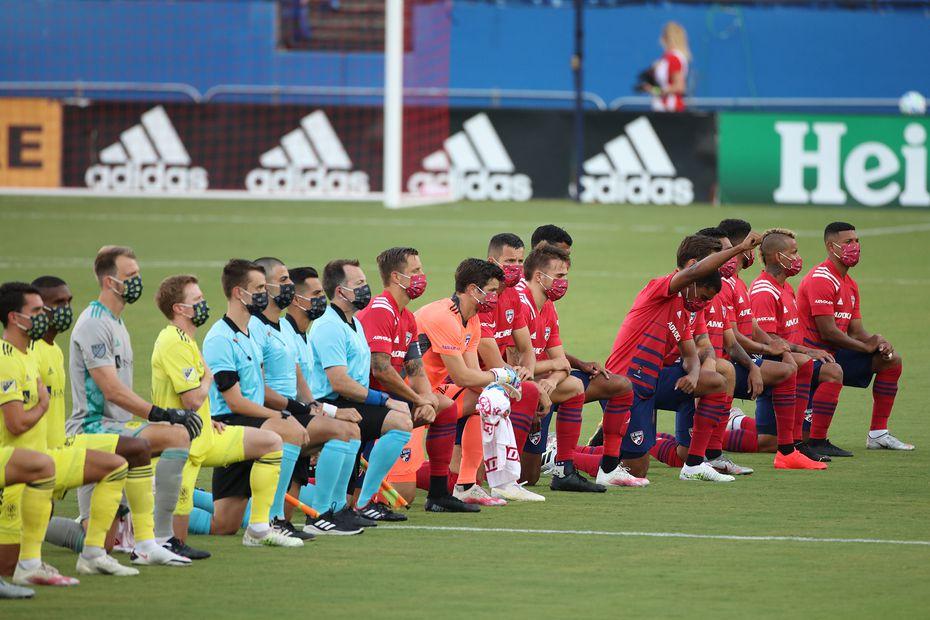Los jugadores del FC Dallas (rojo), los del Nashville FC y los árbitros del partido, se arrodillan durante la entonación del himno nacional, el 12 de agosto de 2020 en el Toyota Stadium de Frisco.