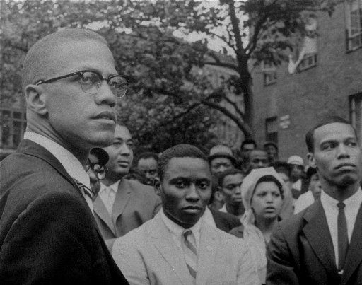 Black Nationalist leader Malcolm X (left) is shown at a 1963 rally in Harlem. (Louis Farrakhan, at the time chief minister of the Nation of Islam's Boston mosque, is at the far right.) (AP file photo)