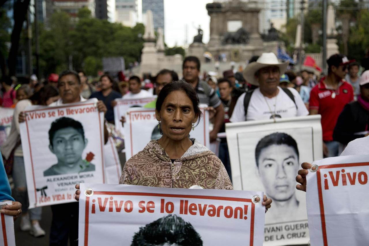 Marchers went through  the streets of Mexico City in August carrying banners bearing pictures of some of the 43 students who disappeared in southern Guerrero state in 2014. The case remains unsolved.