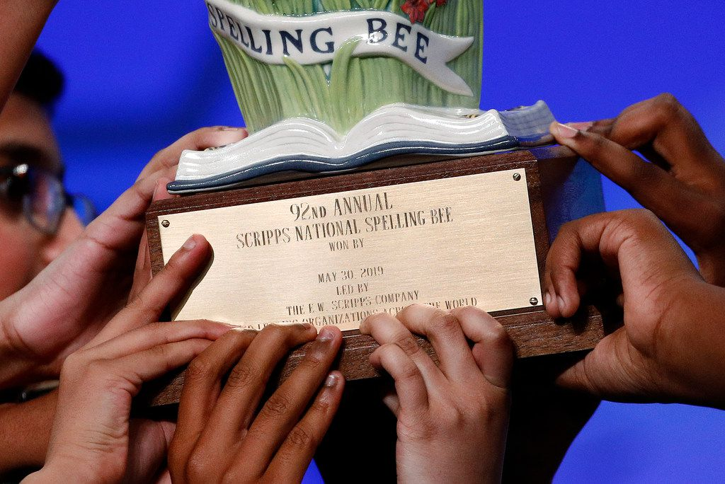 Eight co-champions carry a trophy after winning the 2019 Scripps National Spelling Bee.