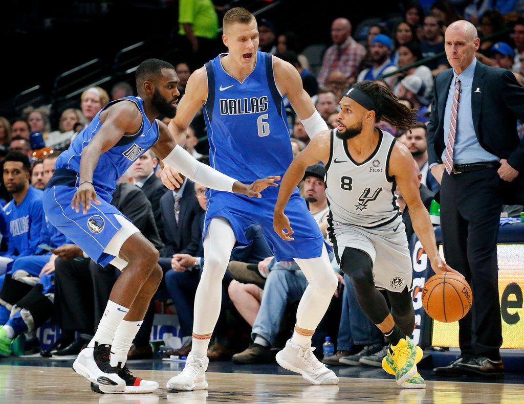 Dallas Mavericks forward Kristaps Porzingis (6)  and guard Tim Hardaway Jr. (11) pressure San Antonio Spurs guard Patty Mills (8) during the second quarter at the American Airlines Center in Dallas, Monday, November 18, 2019. (Tom Fox/The Dallas Morning News)