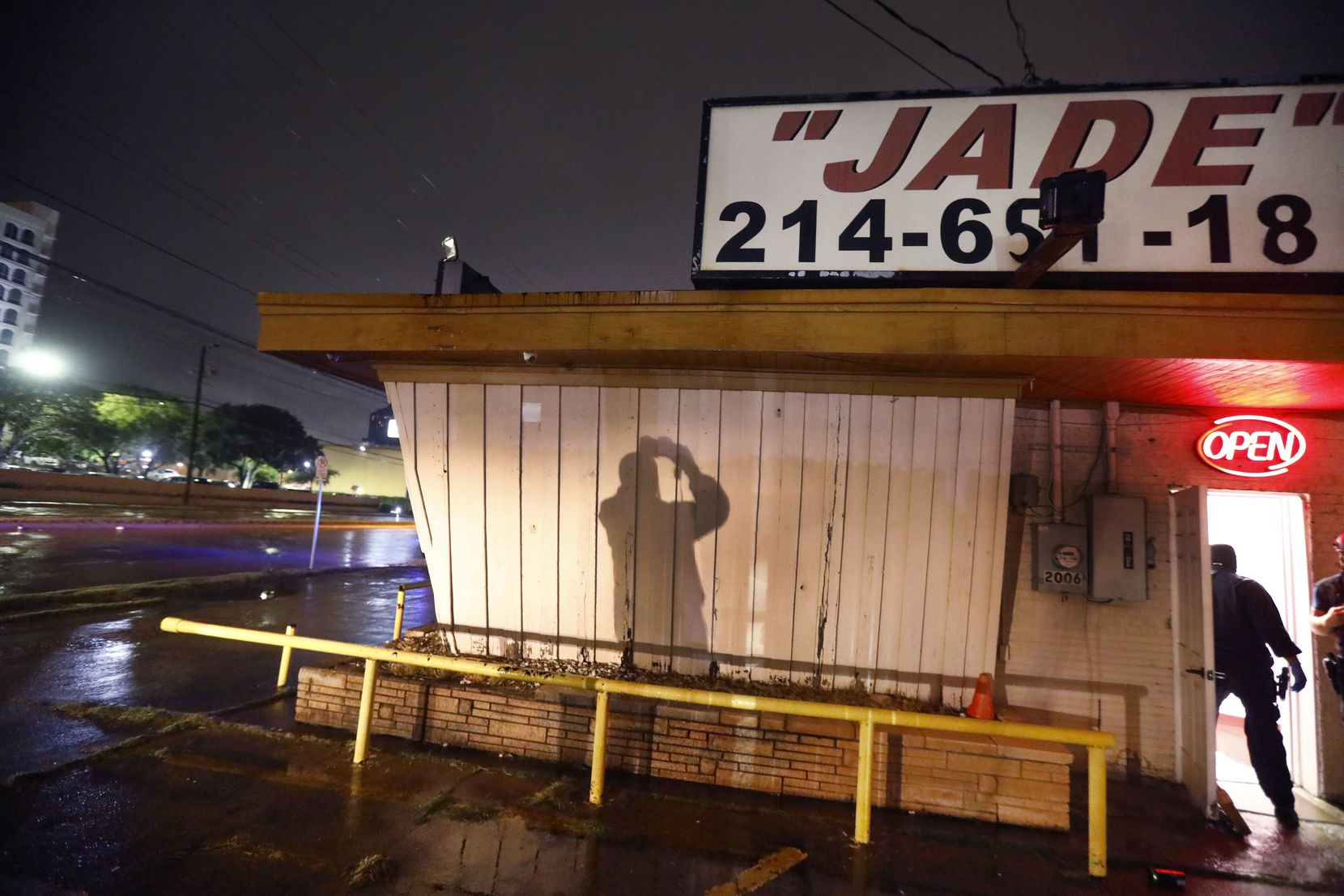 A Dallas Police vice officer takes photos of the outside of Jade Spa, a lucrative massage parlor raided on Market Center Boulevard near the Hilton Anatole Wednesday morning.
