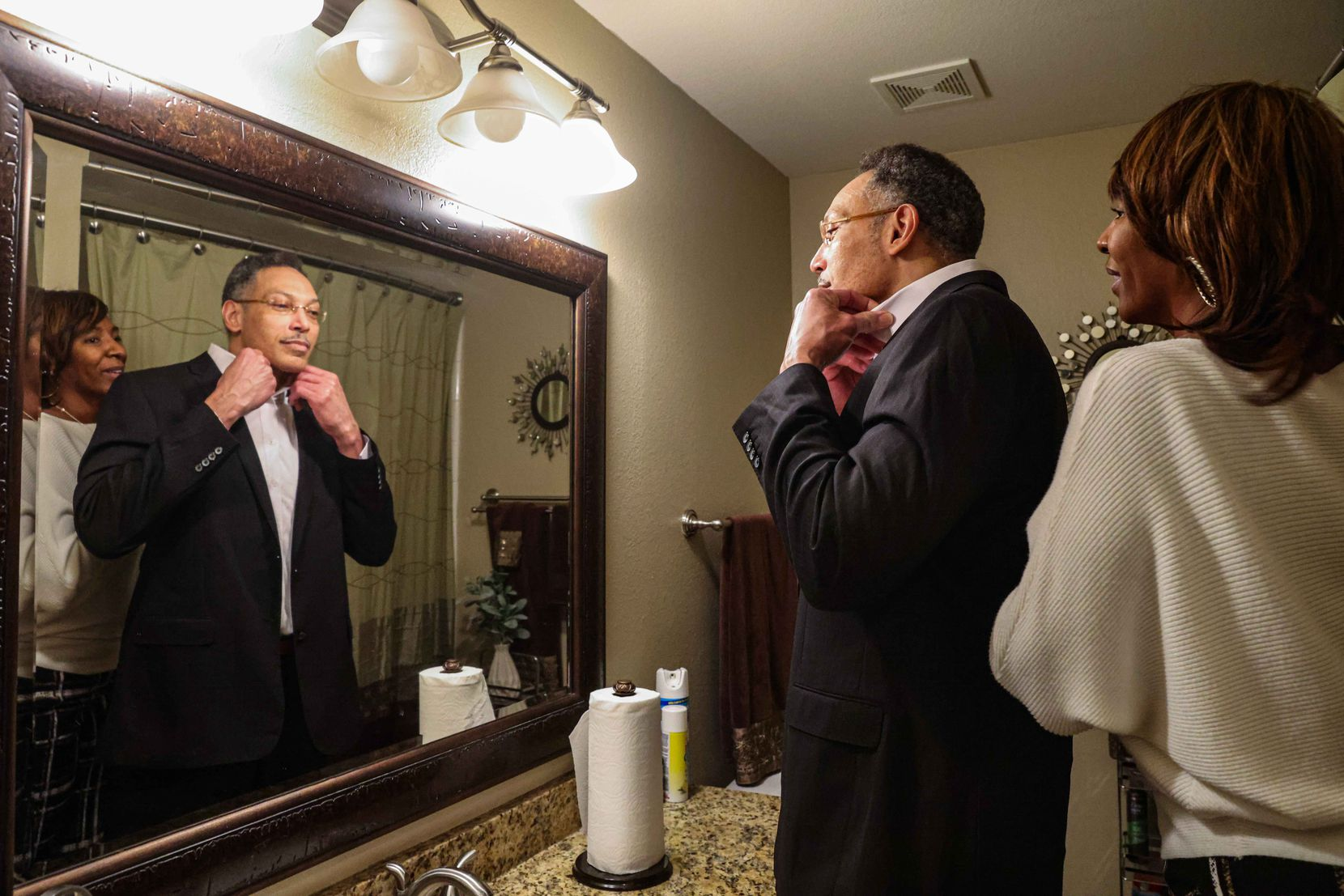 Ben Spencer checks himself out in a bathroom mirror with his ex-wife Debra Spencer at their home in Cedar Hill after he was released from the Dallas County jail on Friday, March 12, 2021. Debra Spencer never stopped supporting him even though they divorced while he was in prison.