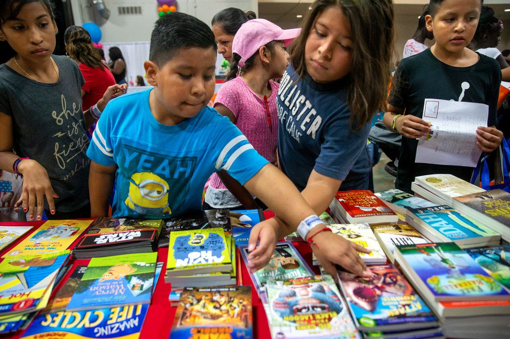 Danny Perez, 9 (second from left), and Christopher Romero, 12 (second from right), pick out free books during the 23rd annual Mayor's Back to School Fair at the Fair Park Centennial Hall in Dallas on Friday, Aug. 2, 2019. Thousands of children and their family members were expected to attend, and the event included health and eye screenings, dental screenings, backpack giveaways and more.