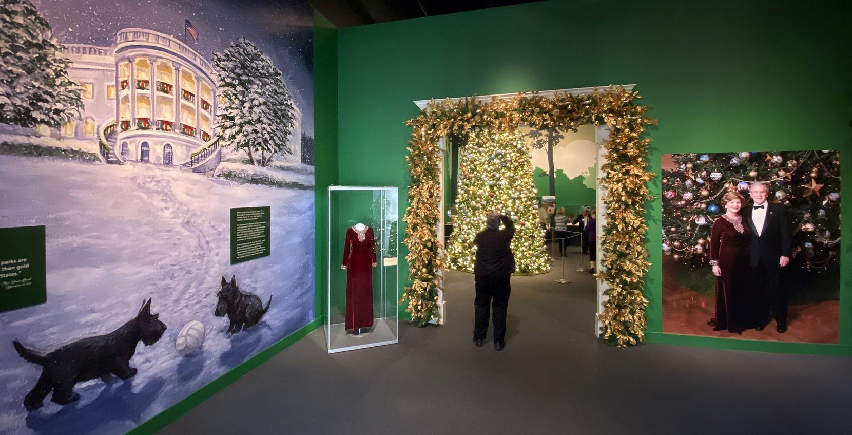 A visitor photographs an 18-foot replica of the official White House Blue Room Christmas tree from 2007 in the entryway of Holiday in the National Parks exhibit at the George W. Bush Presidential Center in University Park.