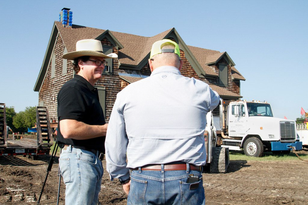 Clint Haggard talks with family friend Jeff Nesbitt in front of the Collinwood Home, built around 1861, as it is prepared to be moved to the Haggard farm in Plano.