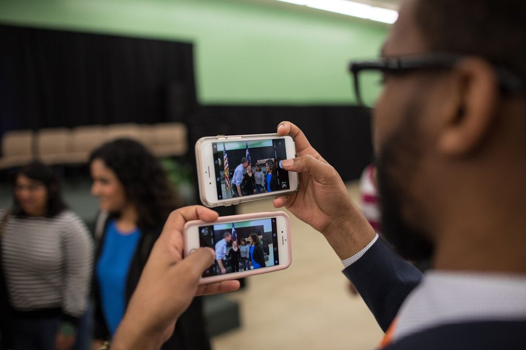 Dexter McCoy holds two cellphones as he takes pictures of Rep. Beto O'Rourke with supporters after a town hall event at Greenhouse International Church in Houston.