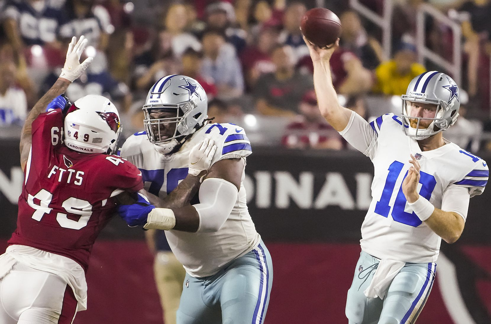 Dallas Cowboys quarterback Cooper Rush (10) throws a pass as tackle Ty Nsekhe (79) blocks against Arizona Cardinals linebacker Kylie Fitts (49) during the second quarter of an NFL football game at State Farm Stadium on Friday, Aug. 13, 2021, in Glendale, Ariz.