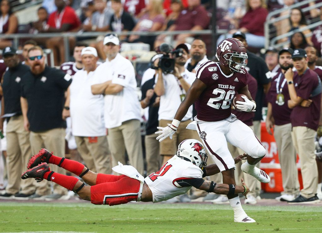 Isaiah Spiller #28 of the Texas A&M Aggies is tackled from behind by Michael Lawson #41 of the Lamar Cardinals during the second quarter at Kyle Field on September 14, 2019 in College Station, Texas.