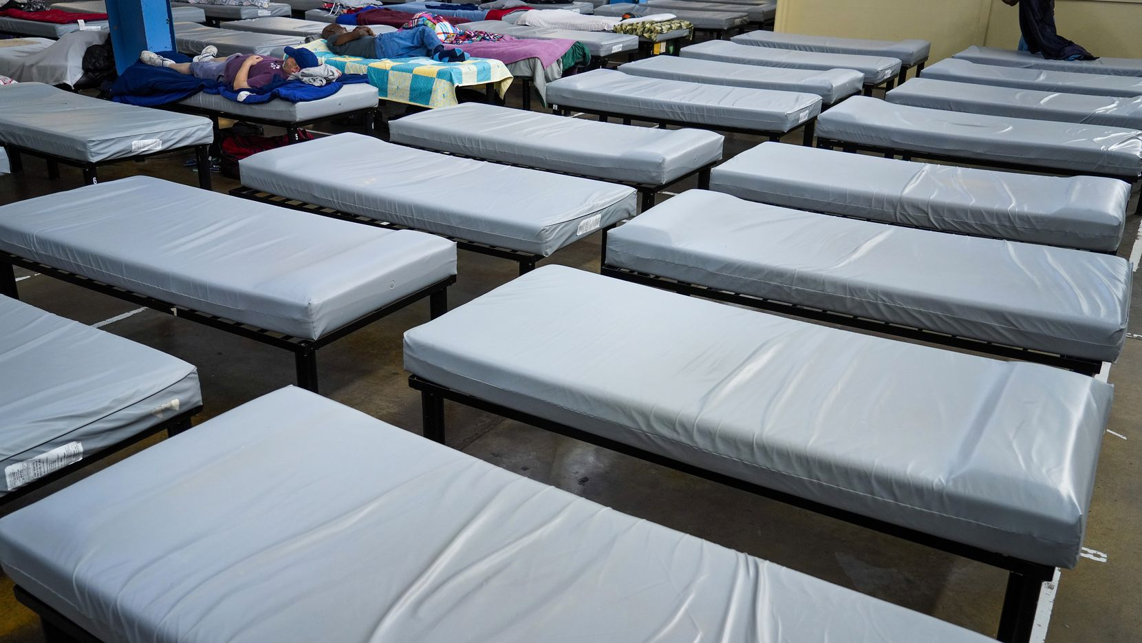 Beds are lined up at Austin Street Center on Wednesday, March 11, 2020, in Dallas.  Shelter providers at Austin Street two days later removed 37 beds, about 10% of its total capacity, to distance guests to prevent the spread of coronavirus.
