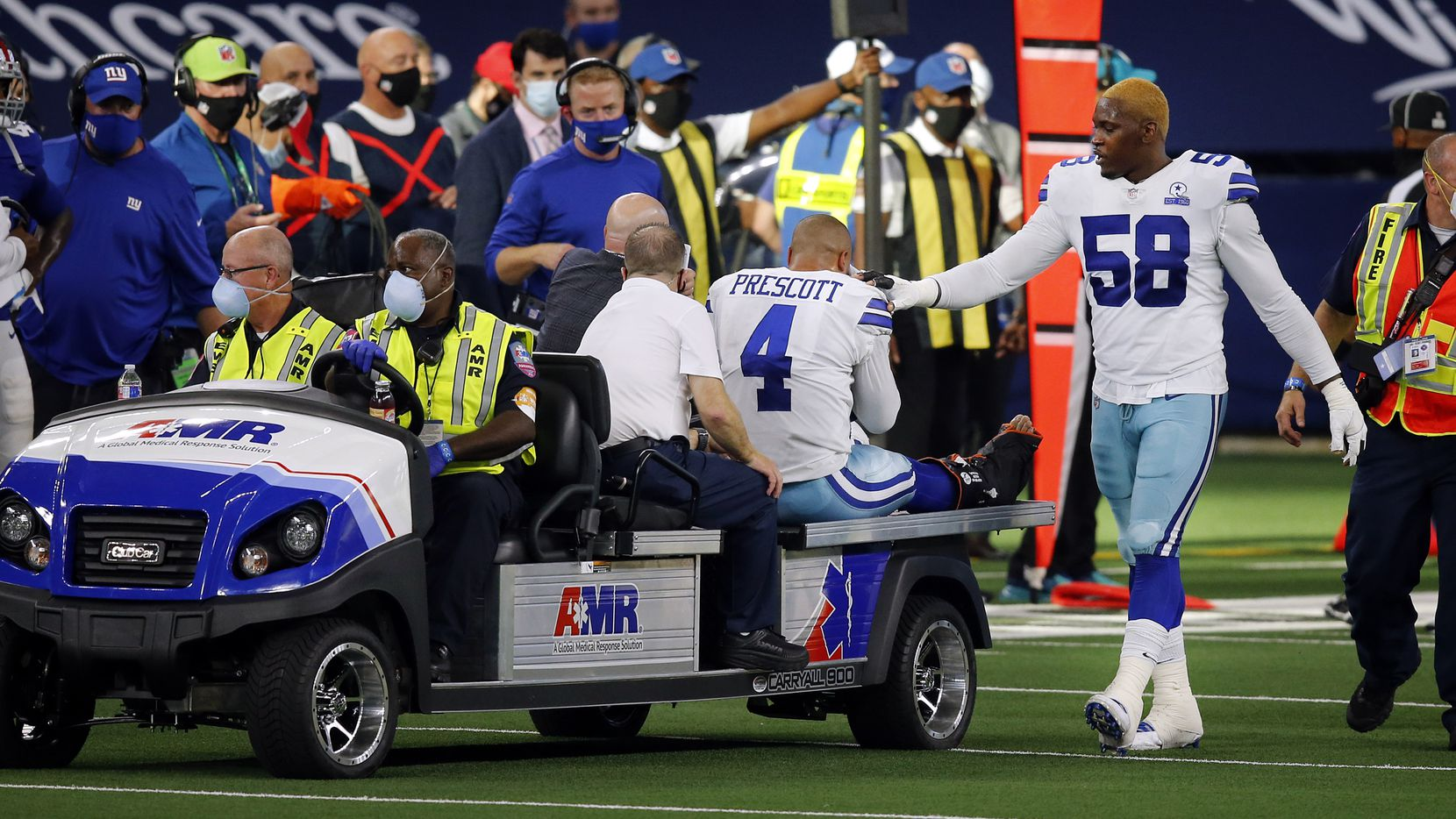 Cowboys defensive end Aldon Smith (58) comforts quarterback Dak Prescott (4) as he's carted off the field with an ankle injury during a game against the Giants at AT&T Stadium in Arlington on Sunday, Oct. 11, 2020.