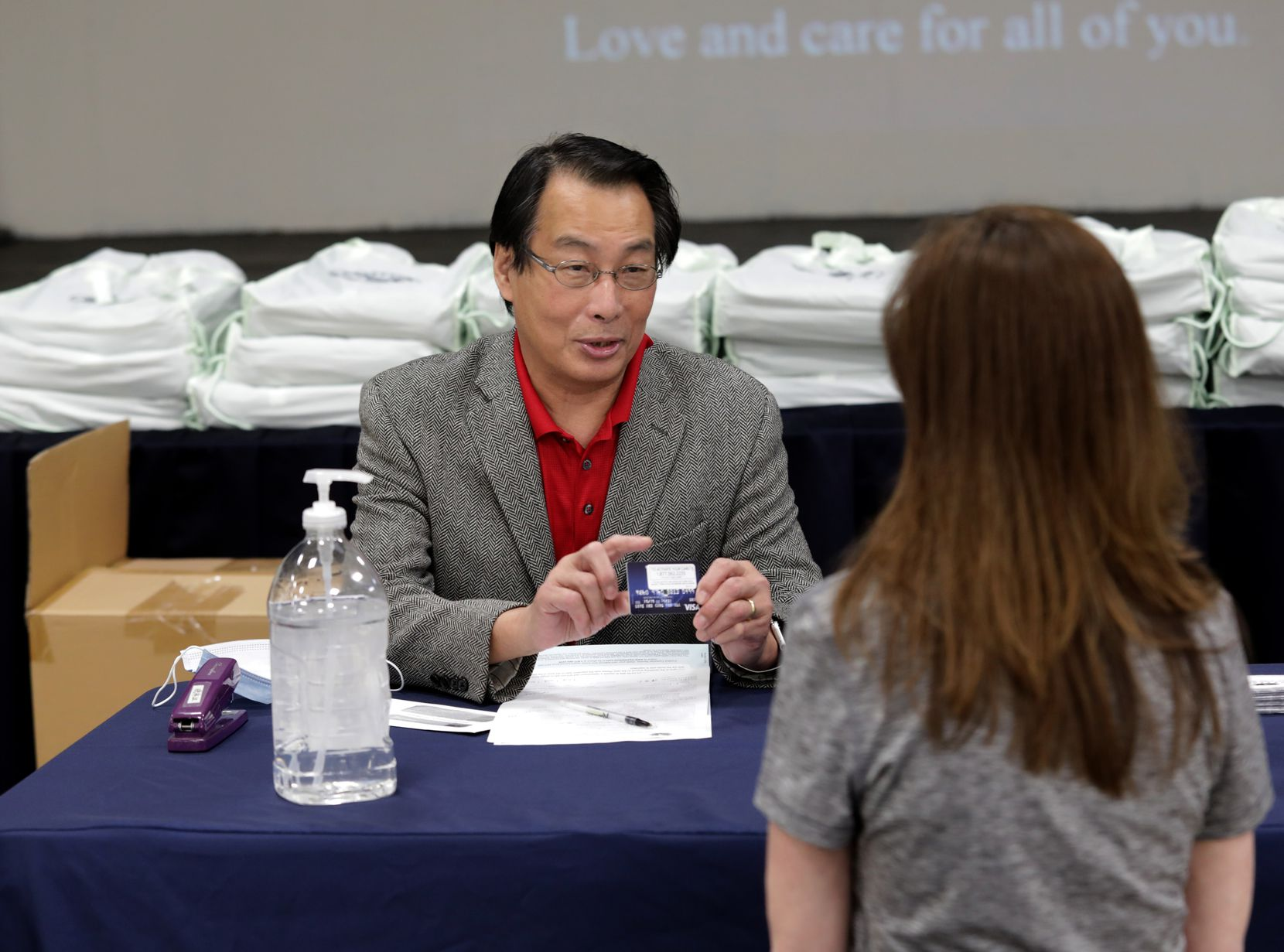 Addison mayor Joe Chow, left, displays a pre-paid giftcard to Tia Bourne.  The cards are being given to families displaced in a recent Addison fire as they receive help at the Tzu Chi foundation in Richardson, TX, on Apr. 25, 2021. (Jason Janik/Special Contributor)