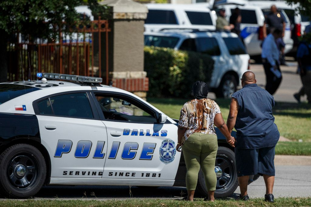 Bystanders watch as Dallas Police Department SWAT officers work the scene where someone shot at officers attempting to make an arrest at an east Oak Cliff apartment complex, police said, on Thursday, July 13, 2017, in Dallas.