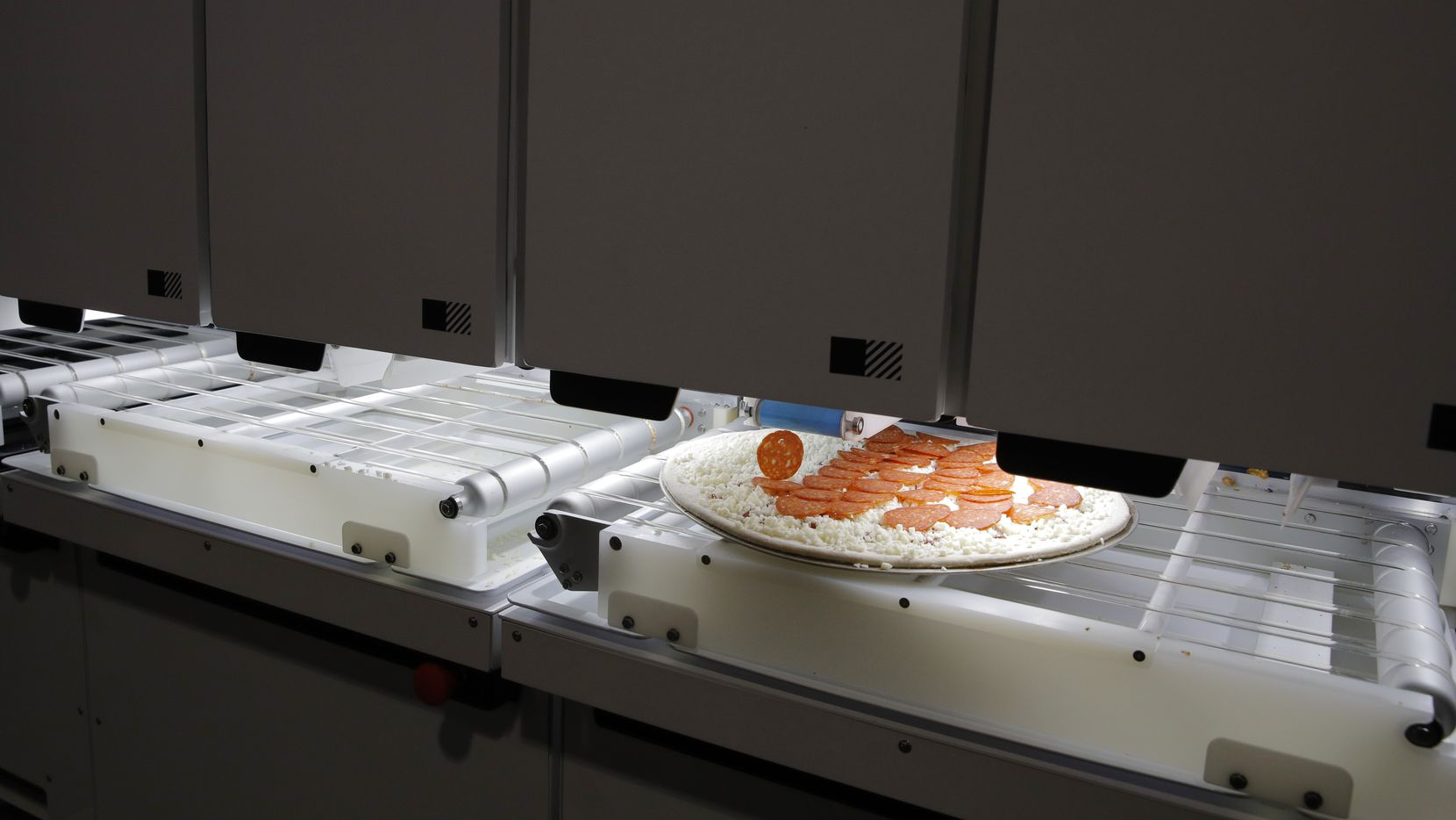 Picnic's pizza-making robot makes a pizza at a food vendor's booth during the CES tech show on Wednesday in Las Vegas. (AP Photo/John Locher)