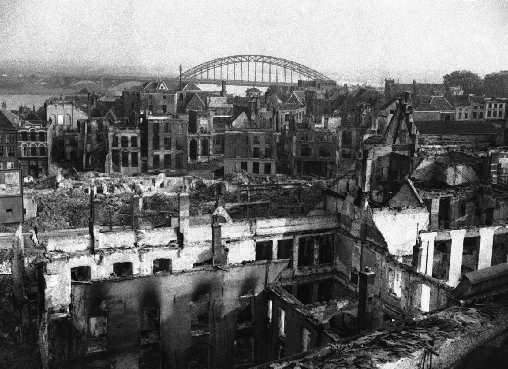 A view of bomb-wrecked and shell-shattered Nijmegen, Netherlands in February, 1945, with the famous bridge over the river Waal in the background. Only the shells of some houses are left in the town, which has seen some of the most fierce fighting of the war. Most of the buildings were razed to the ground.