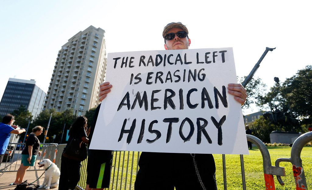 Frank Darbo holds a sign as crew members work to remove the Robert E. Lee statue in the background at Robert E. Lee Park in Dallas, Thursday, Sept. 14, 2017.