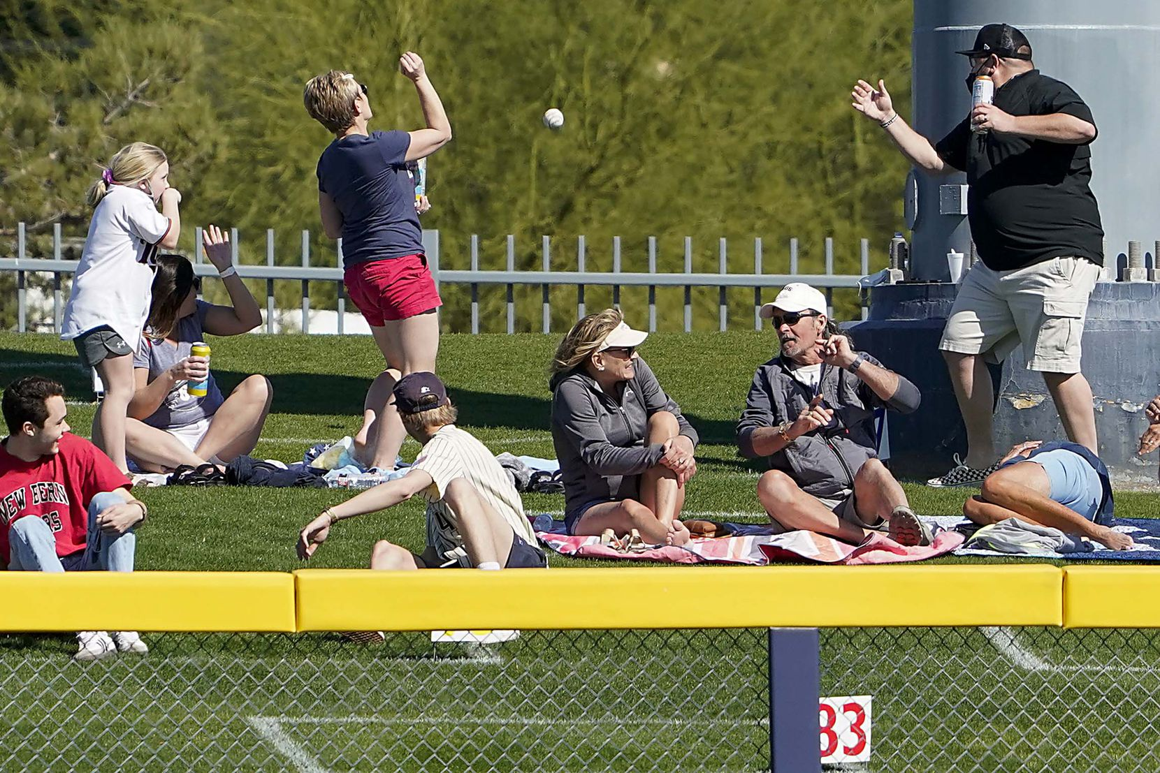 Fans reach for the ball on a solo home run by Texas Rangers outfielder during the fifth inning of a spring training game against the Seattle Mariners at Peoria Sports Complex on Wednesday, March 10, 2021, in Peoria, Ariz.