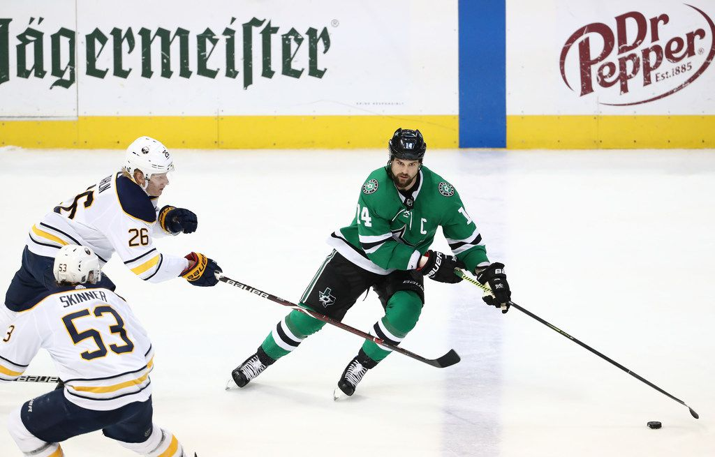 DALLAS, TEXAS - JANUARY 30:  Jamie Benn #14 of the Dallas Stars skates the puck against Rasmus Dahlin #26 of the Buffalo Sabres in the third period at American Airlines Center on January 30, 2019 in Dallas, Texas. (Photo by Ronald Martinez/Getty Images)
