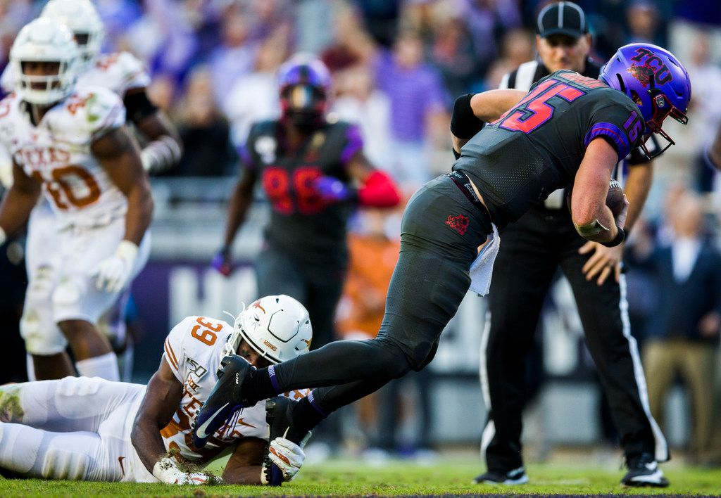 FILE - TCU quarterback Max Duggan (15) falls into the end zone for a touchdown while being tripped up by Texas defensive back Montrell Estell (39) during the fourth quarter of a game on Saturday, Oct. 26, 2019, at Amon G Carter Stadium in Fort Worth.