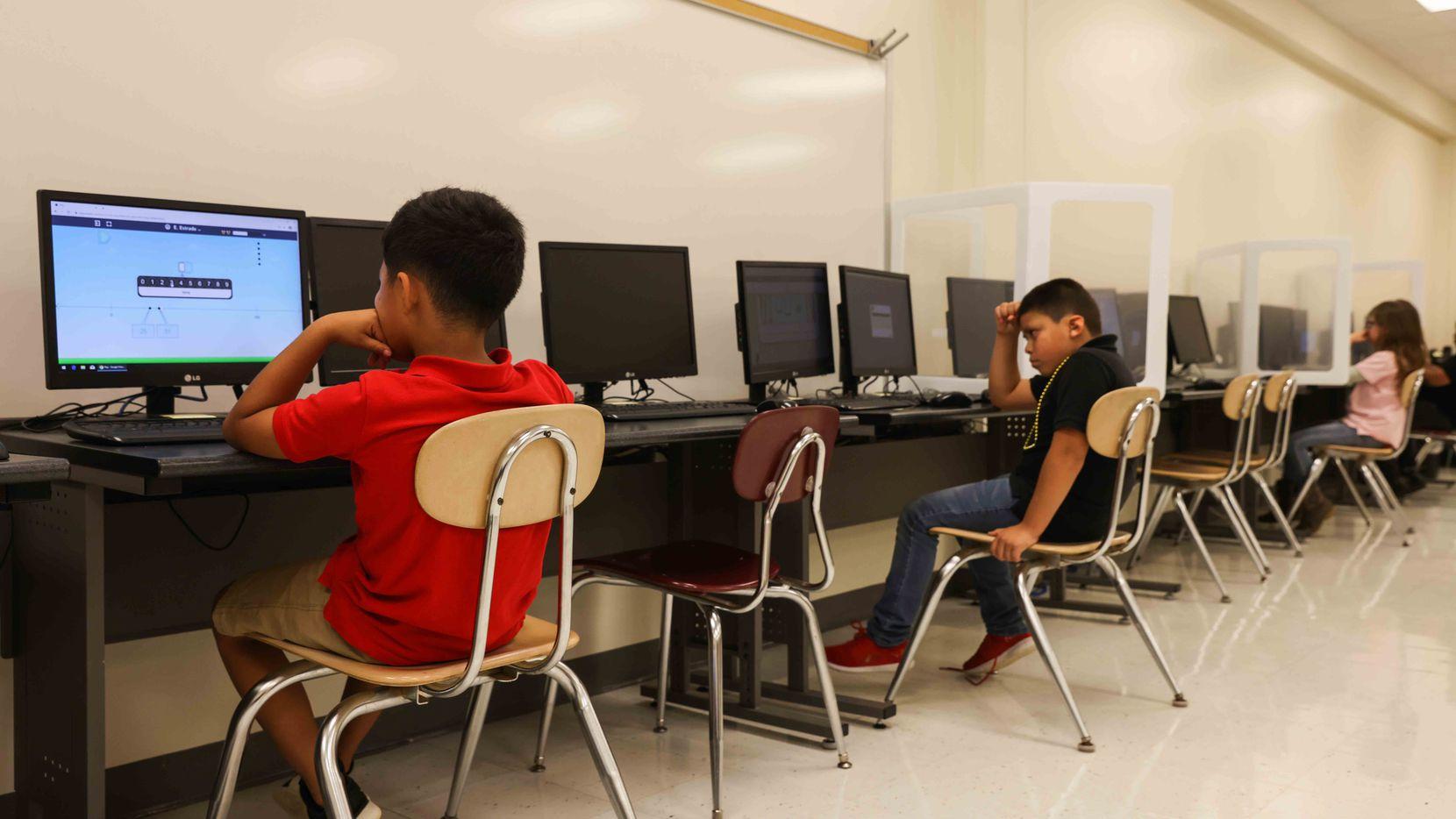 (Desde la izq.) Los estudiantes Evan Estradan, Francisco Rivera y Ashlyn Moorehead participan de un programa después de clases en la primaria Southside en Palestine,Texas.